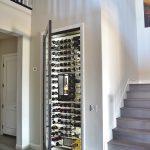 Modern Wine Cellar White Walls Railing Stairs Wooden Floor Black Framed Wine Cellar Door Glass Door Wine Rack Artwork