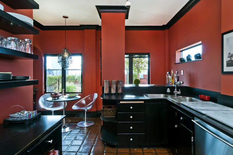 red and black kitchen black cabinets countertop red wall wall mounted shelves ghost chairs pedestal table sinks drawers