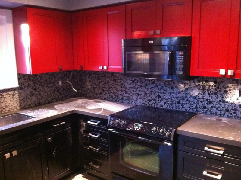 red and black kitchen red top cabinets black cabinets stovetop microwave oven backsplash countertop sink window