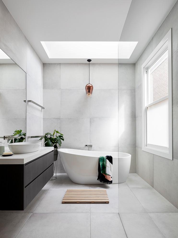 skylight golden light pendant light tiled wall tiled floor freestanding tub glass siding floating cabinet dark cabinet vessel sink window