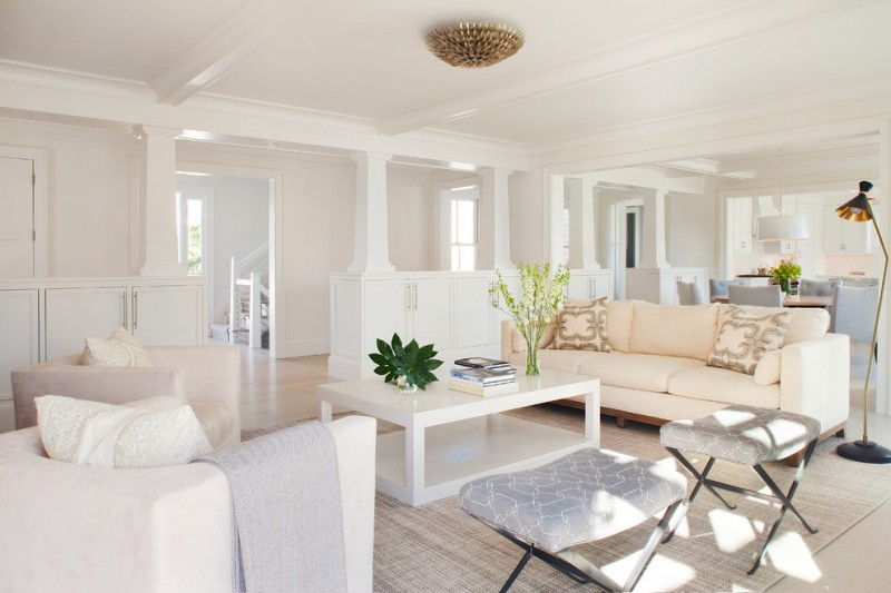white wall white couch beige sofa white coffee table stools rug area room divider standing lamp gold sconce eat in space pendant light hardwood floor