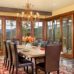 Brown Dining Room Chair Wooden Dining Table Red Patterned Rug Wooden Framed Glass Windows Glass Doors Chandelier