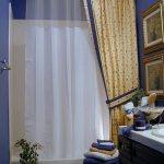 Ceiling Track Shower Curtain Transparent Curtain Yellow Patterned Curtain Blue Walls White Tile Towels Vanity Sink Bath Mat