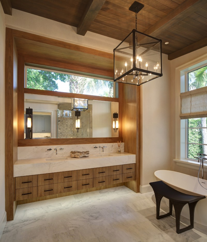 double vanity wall mirror glass chandelier rustic wall sconces glass windows freestanding tub wooden bench drawers roman shade