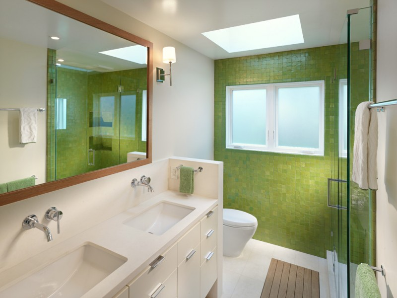 double vanity wall mirror green wall tile white top sinks faucets drawers wall sconces wooden frame mirror towel bar bath mat