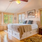 Full Storage Platform Bed Ceiling Fan With Lamp Windows Beige Blanket Wall Sconces Artwork Wooden Nighstand Area Rug