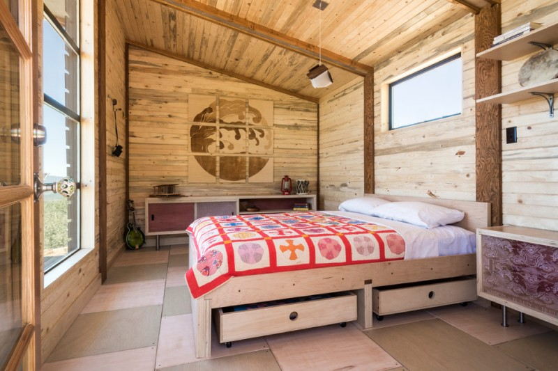 full storage platform bed sloped ceiling pendant lamp windows colorful bedding wheeled storage wooden shelves