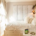 Full Storage Platform Bed White Chic Bedding Beige Curtains Windows Shelves Table Beige Walls Rustic Wall Sconce