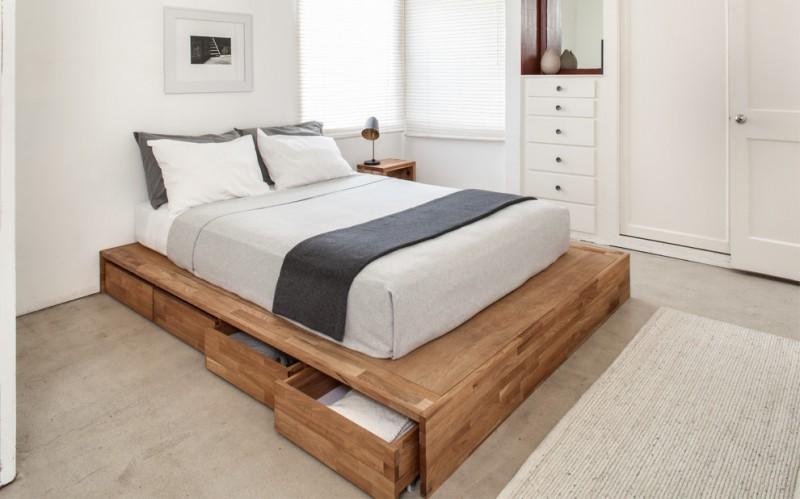 full storage platform bed wooden platform grey bedding wooden side table industrial table lamp rug drawers corner windows