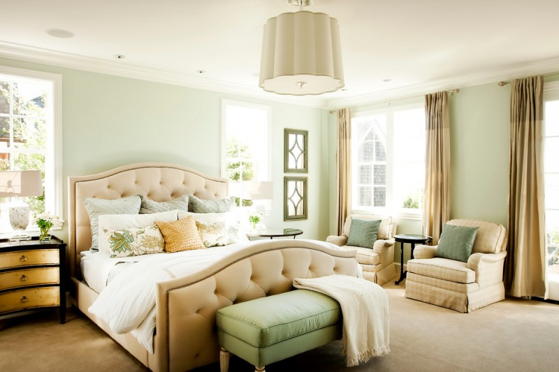 green bedroom walls beige bed tufted headboard green bench armchairs windows ceiling lamp brown curtains nightstands side table