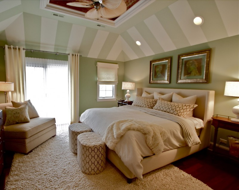 green bedroom walls striped ceiling beige bed headboard white bedding shag rug stools couch table lamps curtains window
