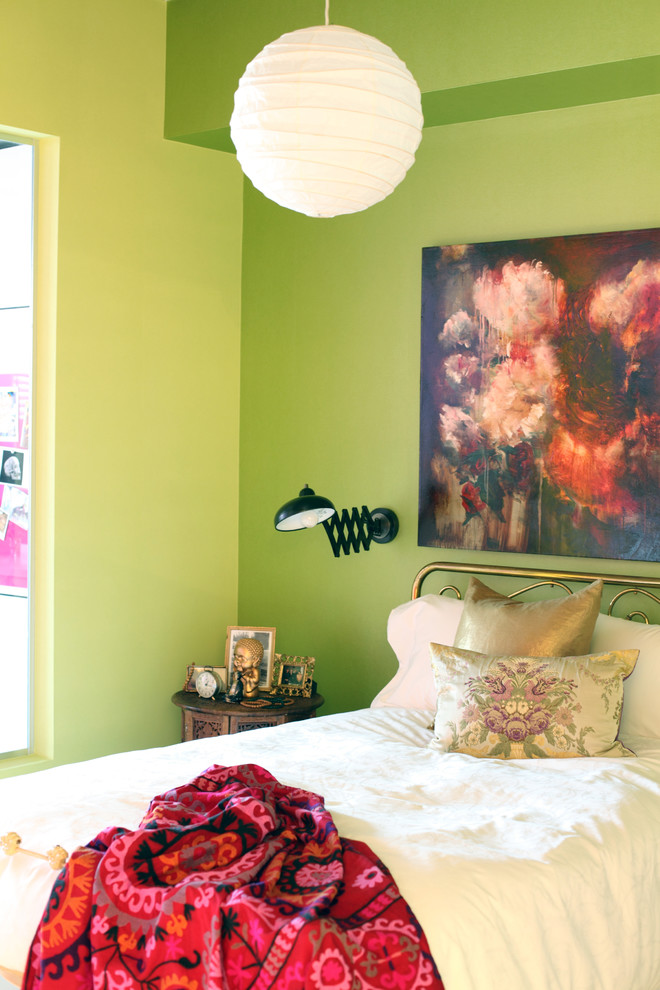 green bedroom walls white chandelier artwork black wall sconce wooden side table red patterned throw gold iron headboard white bedding