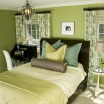 Green Bedroom Walls Wooden Bed Headboard Green Bedding Glass Side Table Chandelier Table Lamp Black Desk White Chair Wndows Green Curtains Green Shades