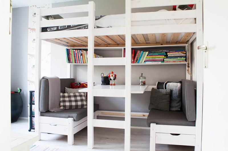 kids white loft bed white built in seating and table shelves grey cushions patterned throw pillows ladder white bedding