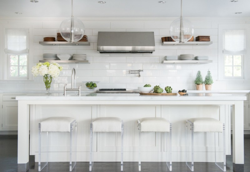kitchen stool acrylic stools white island white cabinets glass pendant lamps range hood stovetop sink white countertops small windows wall shelves