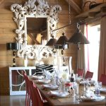 Large Ornate Mirror Brown Ceiling Pendants Wooden Table Red Chairs White Framed Mrror Mirrored Cabinet Black Table Lamps
