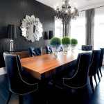 Large Ornate Mirror Dark Blue Chairs Wooden Table Chandelier Black Wallpaper Black Table Lamps Windows Grey Curtains