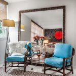 Large Ornate Mirror Floor Lamp Blue Wooden Armchairs Glass Side Table Glass Flower Vases Patterned Rug Window Roman Shade