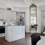 Large Ornate Mirror White Subway Backsplash White Cabinets Shelves Drawers Stovetop Oven White Island Sink Countertop Sofa