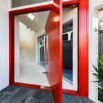 Red Door Designs Large Pivot Door Silver Door Hardware White Walls White Ceiling Grey Floor Tile Glass Windows Wall Sconce