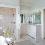 Regal Glass Glass Shower Doors White Vanity Mirror White Wall Sconces Terracotta Floor Grey Bathroom Rug Towel Hook