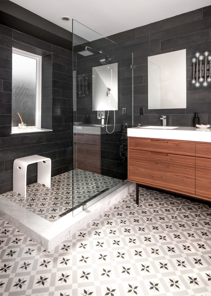 regal glass patterned floor tile wooden bathroom vanity white top black wall tile mirror wall sconce white bench window sink