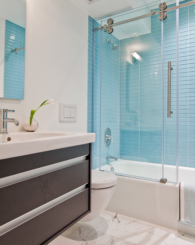 sliding glass shower door blue shower wall tiles mirror shower head white tub toilet marble floor vanity sink faucet