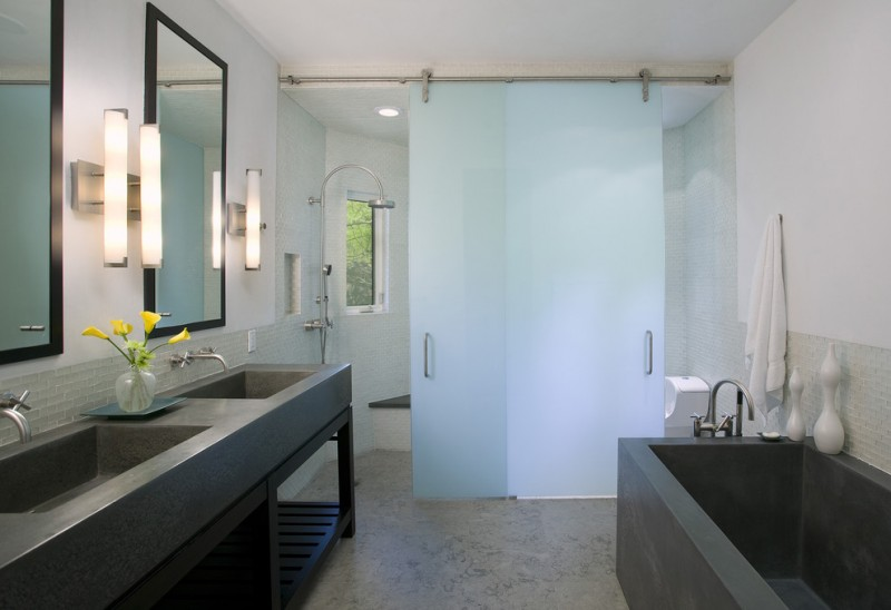 sliding glass shower door frosted glass mirrors wall sconces black bathtub tub filler towel holder grey vanity sinks