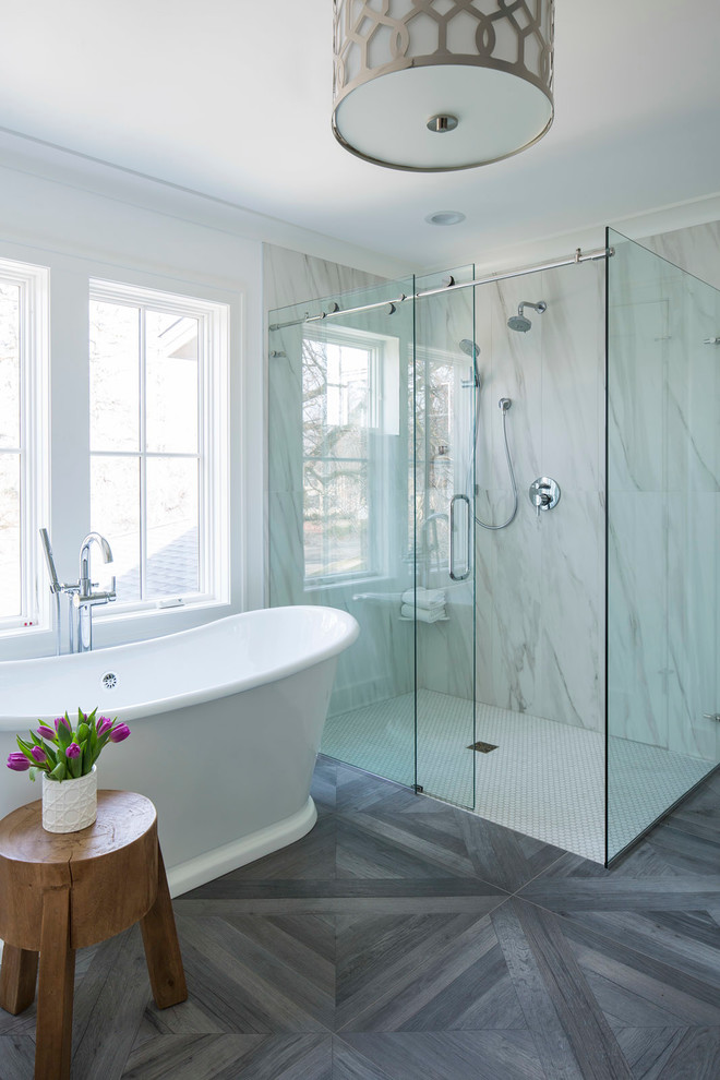sliding glass shower door grey floor tile freestanding bathtub wooden side table chandelier marble wall windows shower head