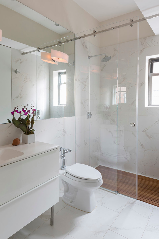 sliding glass shower door white vanity white sink toilet wall sconce white floor tile bamboo shower flooring window mirror