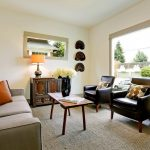 Small Coffee Table Minimalist Wooden Table Grey Sofa Black Leathered Armchairs Black Vase Windows Indoor Plant Area Rug