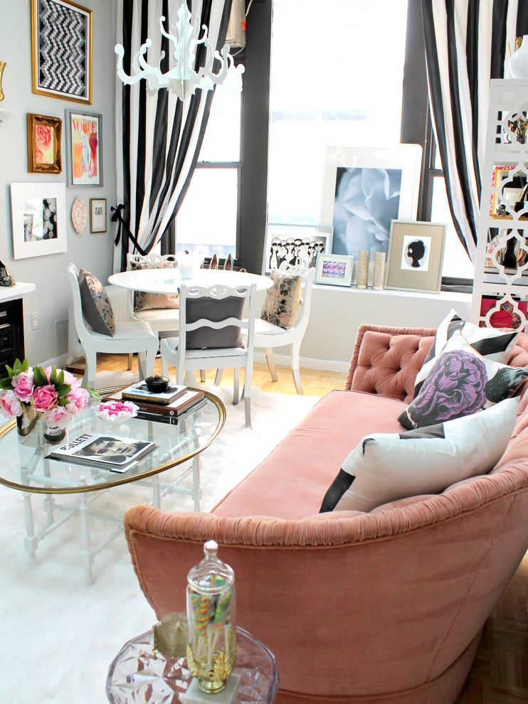 small coffee table pink tufted sofa white chandelier black and white striped curtains white area rug glass tables decorations