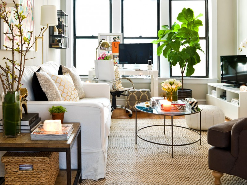small coffee table white sofa white and grey stools indoor plant wall sconce tv cabinet area rug windows armchair side table