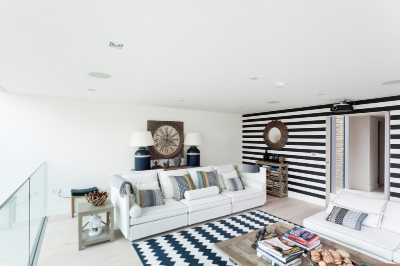 striped wall painting monochrome stripe area rug white sofas wooden table wooden side tablw white wall table lamps glass railing