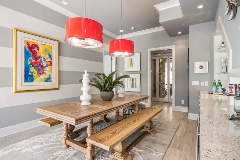 striped wall painting red pedant lamps wooden table wooden bench marble countertop grey and white walls ceiling area rug shelves