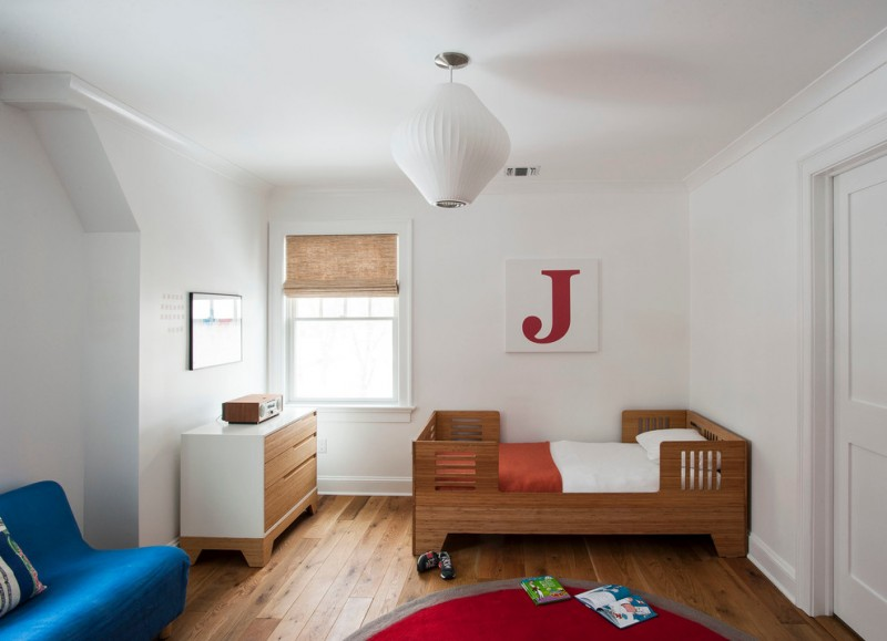 toddler boys bed letter art pendant lamp white walls wooden bed drawers blue couch red rug wooden floor window rattan shade