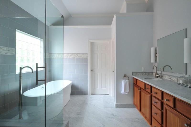 acrylic freestanding bathtub blue wall tile glass shower doors towel rink wooden vanity granite top wall sconces mirror sink faucet window