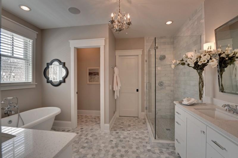 acrylic freestanding bathtub chandelier mirror window blinds tub filler glass shower door white vanity white countertop sink stone floor
