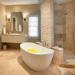 Acrylic Freestanding Bathtub Floating Vanity White Sink Mirror Beige Countertop Wall Sconces Mounted Tub Filler Shower Head Beige Tiles