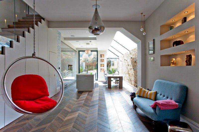 antique silver pendant light glass hanging chair blue sofa herringbone wooden floor built in shelves glass railings recessed lighting