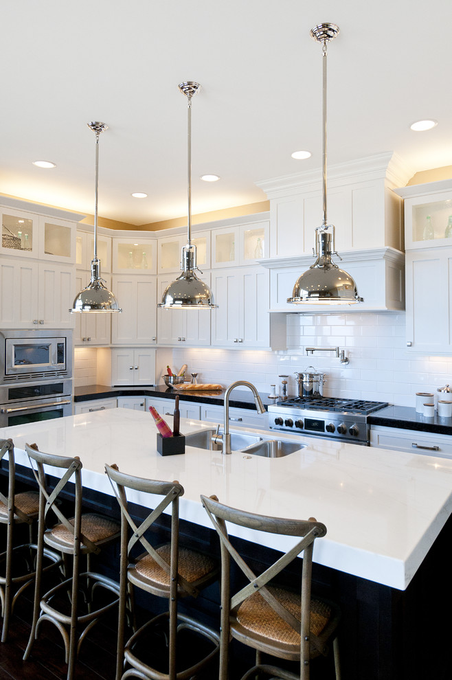 antique silver pendant light white and black countertop black island white cabinets stove oven range hood wooden barstools oven microwave sink white backsplash