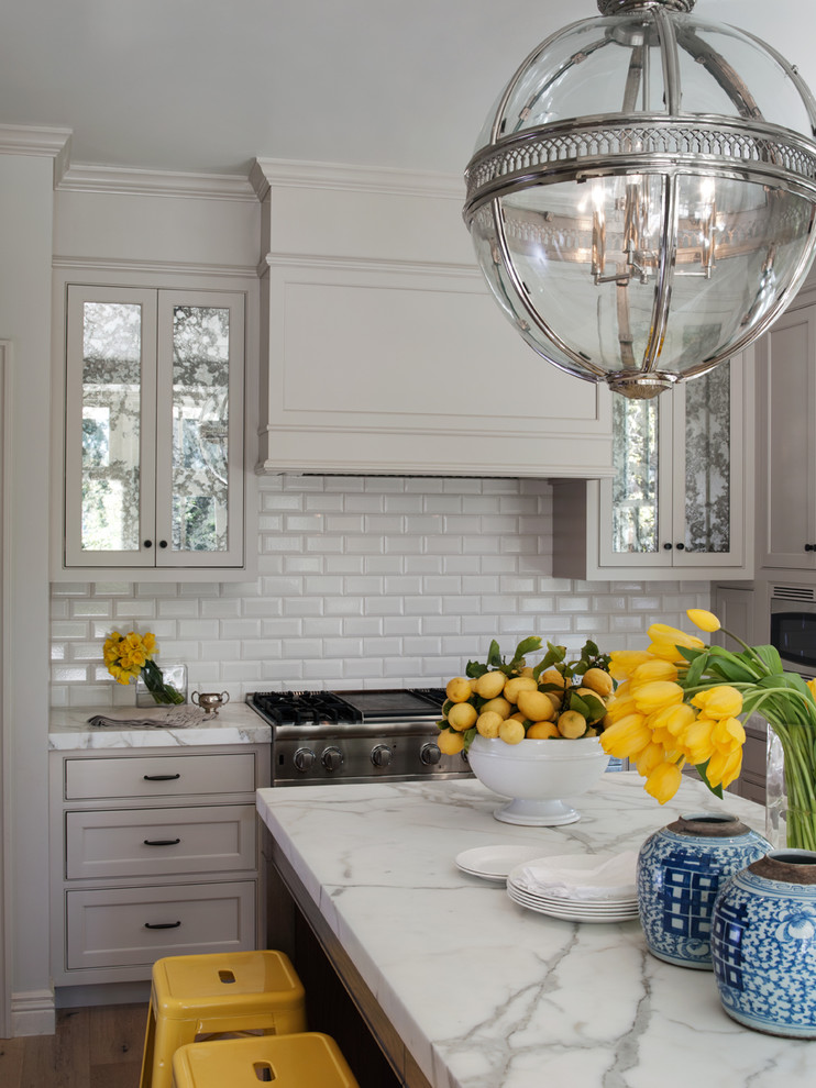 antique silver pendant light white subway backsplash stove oven range hood white marble countertop drawers island yellow stools