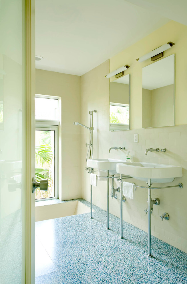 bathroom with grey marble floor, white wall, two white sinks, two mirrors, one lowered bathtub