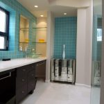 Bathroom With White Floor, Wooden Cabinet With White Marble Top, Blue Ceramic Wall, Blue Sink, Metallic Small Cabinet