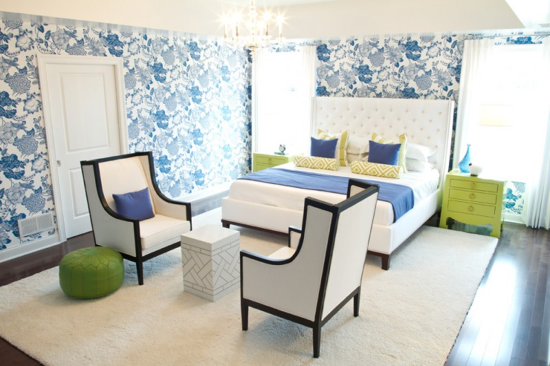 bedroom with dark wooden floor, white fur rug, white chairs, white square stool for table, neon green night stand, white bedding with white blue linen, blue flower wallpaper