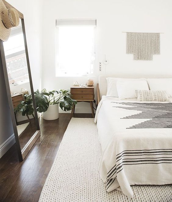 bedroom with dark wooden floring, white rug, wooden side table with cabinet, white bed, large mirror