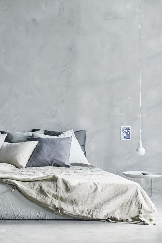 bedroom with light grey wall, white flooring, large bed with monochrome linen, white hanging lamp, white side table