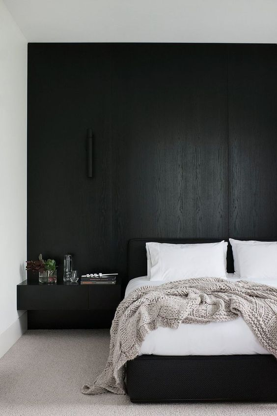 bedroom with nude rug, white wall, black built in side table, black wooden wall on the head of the table, black bedding, white linen