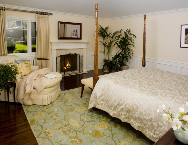 bedroom with plants pattern rug, golden embroidered linen, soft colored couch, fireplace