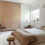 Bedroom With Sliding Wooden Door To Cupboard, White Rug, White Wall, Wooden Side Table, Wooden Stool, Wooden Chair, White Linen Bed